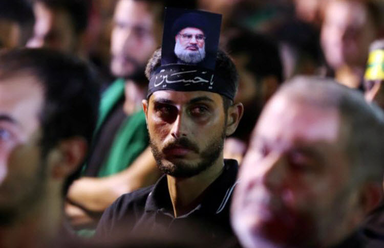 A supporter of Lebanon's Hezbollah leader Hassan Nasrallah has his picture on his head