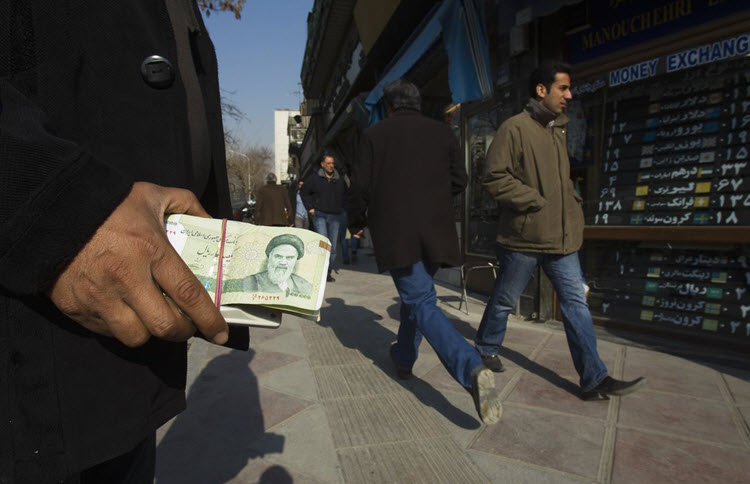 A money changer holds Iranian rial banknotes as he waits for customers in Tehran's business district