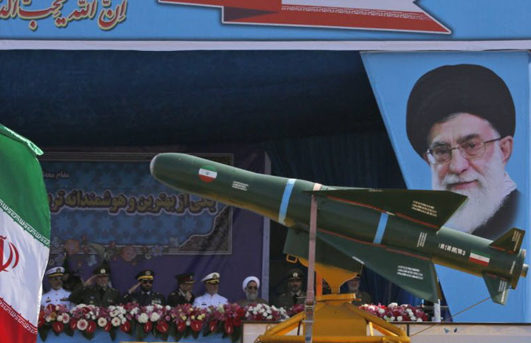 An Iranian military truck carries missiles past a portrait of Iran's Supreme Leader Ayatollah Ali Khamenei