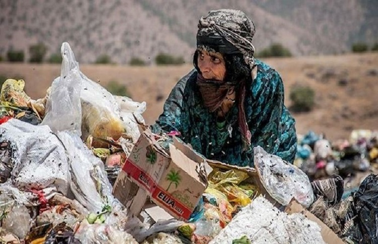 Poor Iranian woman searches in the garbage for food, a glimpse of what is becoming a daily image in Iran
